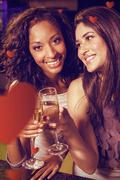Composite image of happy young women having champagne Stock Photos