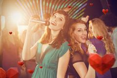 Composite image of two beautiful women singing song together Stock Photos