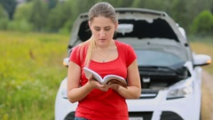 Confused woman standing at brokedown car in the field and reading user manual Stock Footage