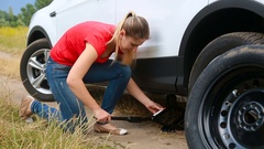 Young woman changing flat tire on car broken at field Stock Footage
