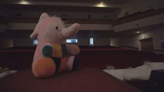 Toy pink plush elephant stands on the stage Stock Footage