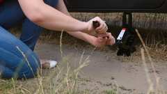 Closeup of young woman lifting broken car with jack screw at field Stock Footage
