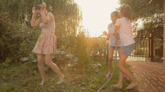 Happy family playing in garden and spilling water over themselves from hose Stock Footage