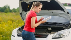 Young woman looking at the car manual and trying to repair brakedown vehicle Stock Footage