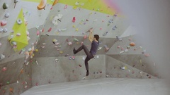 Free climber young fitness man climbing modern artificial boulder in gym Stock Footage