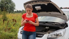 Young worried woman standing next to broken car in field and calling service Stock Footage