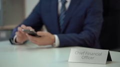 Male chief financial officer texting on smartphone, viewing business files Stock Footage