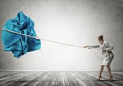 Woman pulling with effort big crumpled ball of paper as creativity sign Stock Photos