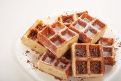 Belgian waffles with grated chocolate and icing on a white plate isolated Stock Photos