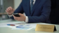 Cost estimator using smartphone, analyzing documents with data for new project Stock Footage