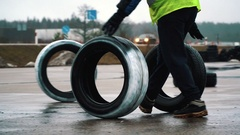 Man rolling tires on race track Stock Footage