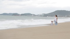 Mother with little daughter walking along the sea in bad weather Stock Footage