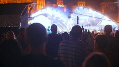 Silhouettes of crowd watching music concert on street at night Stock Footage