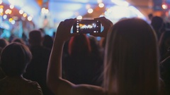 Young woman recording video of music concert on smartphone Stock Footage