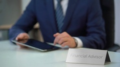 Male financial advisor working on tablet pc, making investment plan for client Stock Footage
