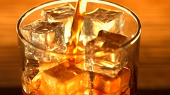 Pouring coke with ice cubes background. Cola with ice and bubbles in glass Stock Footage