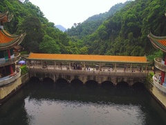 Bridge and tower in Chinese style on lake in  tropical park Stock Footage