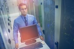 Technician walking with personal computer in hallway Stock Photos