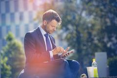 Handsome businessman using mobile phone with food and drink on table Stock Photos