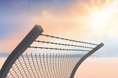 Composite image of bended barbed wire and chainlink fence against white Stock Photos