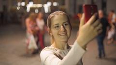 Beautiful smiling woman making selfie shot on smartphone on night street Stock Footage