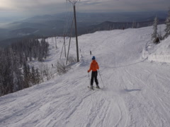 Skier is riding down fast upon ski track on the background of winter vall Stock Footage