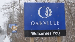 Sign for the town of Oakville. Snow falling. Oakville, Ontario, Canada. Stock Footage