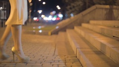 Closeup shot of sexy woman in high heel shoes walking on stone stairs at night Stock Footage