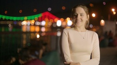 Elegant young woman waiting for boyfriend at river at night Stock Footage