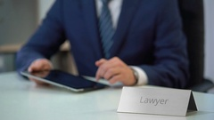 Professional lawyer sliding files on tablet pc touchscreen, working on case Arkistovideo