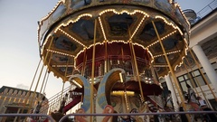 Illuminated vintage carousel in amusement park at evening Stock Footage