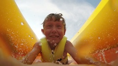 Little boy slides fast by the inflatable slide into the water pool Stock Footage
