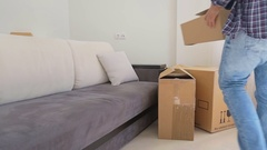 Young couple moving in the new house and carrying carton boxes Stock Footage