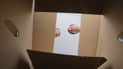 POV of happy young couple opening big cardboard box Stock Footage