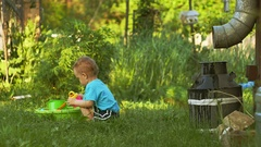 Two years old baby boy plays on backyard in garden with water can Stock Footage