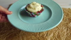 Hand put dessert plate with cupcake on table. Vanilla cupcake with cake cream Stock Footage
