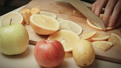 Man Cut Into Slices Of Orange On A Table With Fruit Close Up Stock Footage