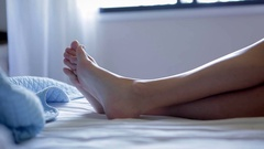 Candid take of girl laid down in bed Close up of feet Stock Footage