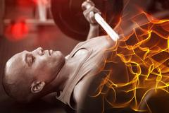 Side view of determined male athlete exercising with barbell Stock Photos