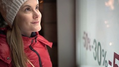 Beautiful attractive young woman looking at shop window. Red winter coat. Sales Stock Footage