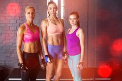 Female athletes standing against wall in gym Stock Photos