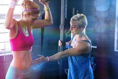Female trainer instructing woman in gym Stock Photos