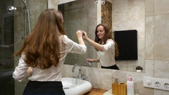 Woman wipe large mirror in apartment bathroom with small piece of paper towel Stock Footage