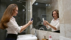 Young woman in formal dress make mirror selfie at home bathroom Stock Footage