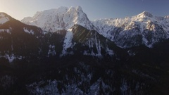 Aerial Pan from Sun Lens Flare on Mountain Top to Snowy Peaks Stock Footage