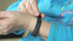 Woman dresses fitness tracker on wrist. Close up Stock Footage