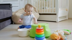 Cute toddler boy sitting on floor at living room and playing with toys Stock Footage