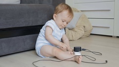 Baby sitting alone in room and playing with sockets and charging wires Stock Footage