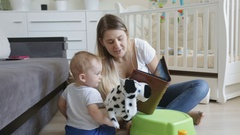 Baby watching photographs in photo album with his mother at living room Stock Footage
