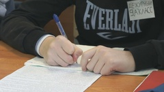 Teenager writes the text in a copybook on a lesson Stock Footage